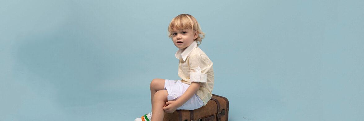 Boy seating on a briefcase box - julesandjuliette